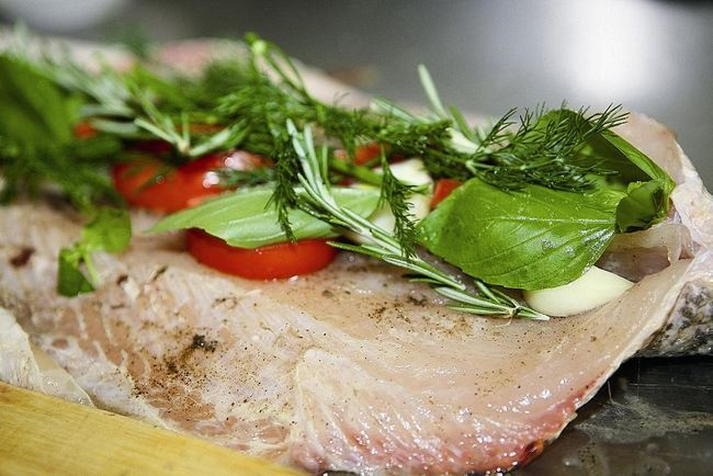 Помістити в голову четвертинки лімона- часник, дольки цибулі, шматочки помідорів і зелень розподілити уздовж хребта.